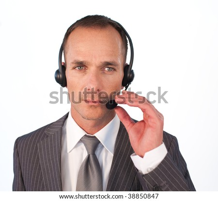 Serious businessman with a headset on looking at the camera