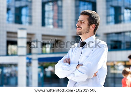 Serious businessman with crossed arms thinking , looking away, outdoor