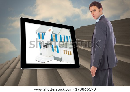 Serious businessman with hand on hip against steps against blue sky