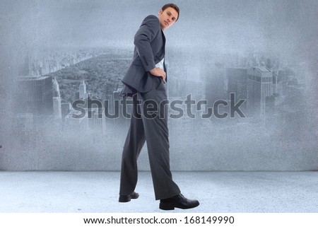 Serious businessman with hands on hips against city scene in a room