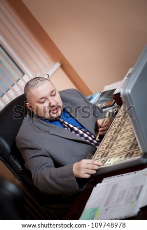 Serious businessman with the suitcase full of dollars is looking on the money. Office background - stock photo