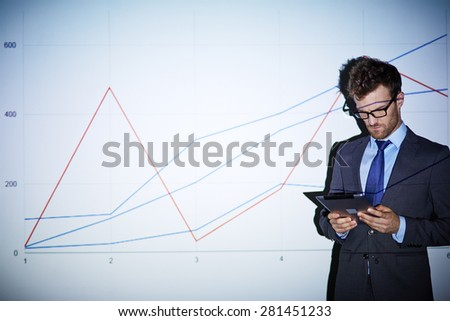 Serious businessman with touchpad standing by wall with graph