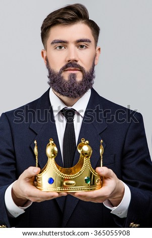Serious businessman, with violet beard and eyebrows, wearing in dark blue suit and tie, holding golden crown on white background, in studio, waist up - stock photo