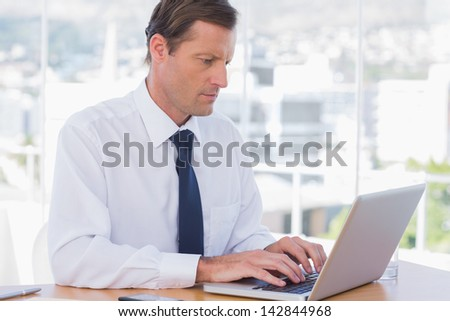 Serious businessman working on a laptop on his desk