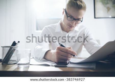 Serious businessman working on documents while sitting at his office, smart phone and glass of water on the table
