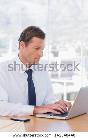 Serious businessman working on laptop on his desk