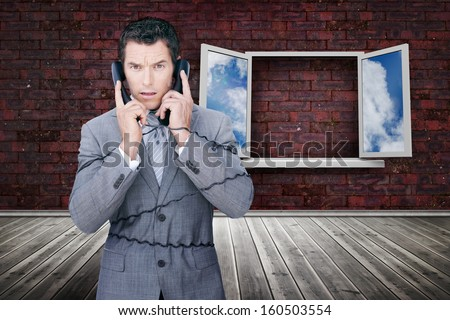 Serious businessman wrapped in cables phoning in front of strange window - stock photo
