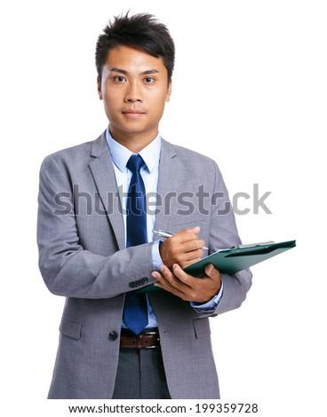 Serious businessman write on clipboard - stock photo