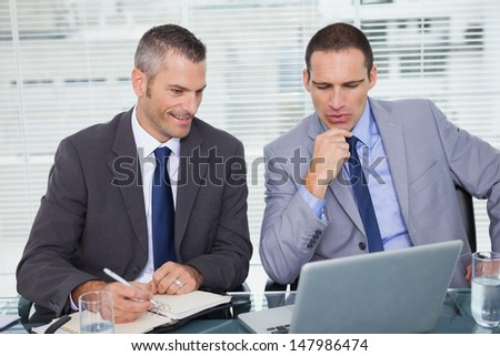 Serious businessmen analyzing application in bright office