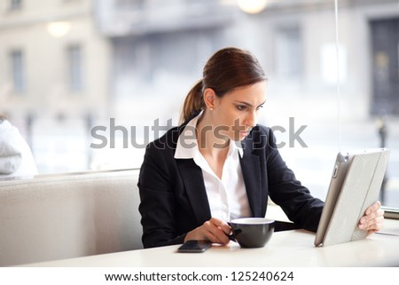 Serious businesswoman drinking coffee / tea and using tablet computer in a coffee shop