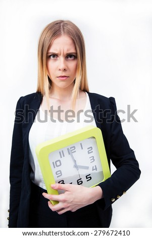 Serious businesswoman holding big clock over gray background and looking at camera - stock photo