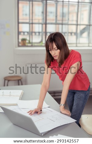 Serious Businesswoman Leaning Against the Worktable with Laptop Computer While Reading Some Documents