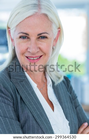 Serious businesswoman looking at camera in office - stock photo
