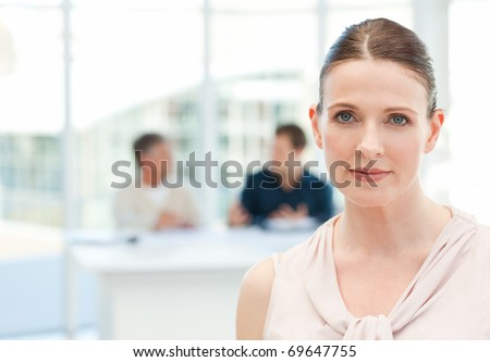 Serious businesswoman looking at the camera while her coworkers are talking in the office - stock photo