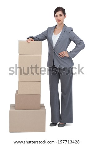 Serious businesswoman posing with cardboard boxes on white background  - stock photo