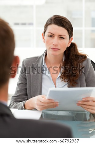 Serious businesswoman questionning a man during a meeting in her office - stock photo