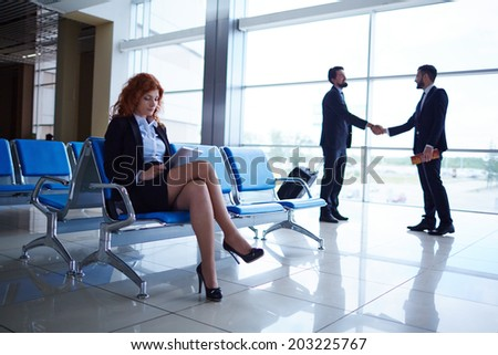 Serious businesswoman sitting in airport on background of her colleagues handshaking by the window