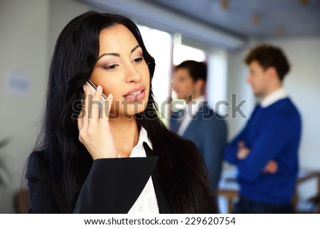 Serious businesswoman talking on the phone with colleagues on background - stock photo