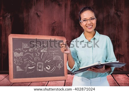 Serious businesswoman wearing glasses taking notes in her clipboard against black board on a wooden table