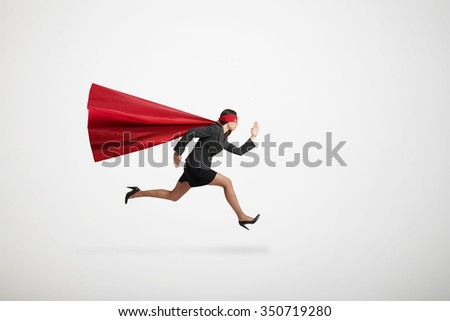serious businesswoman wearing like superhero very fast running over light grey background - stock photo