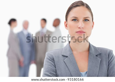 Serious businesswoman with co-workers behind her against a white background - stock photo