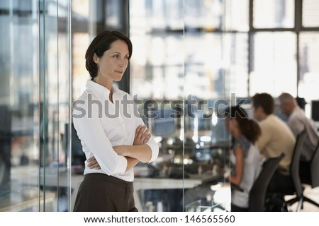 Serious businesswoman with colleagues working in background - stock photo