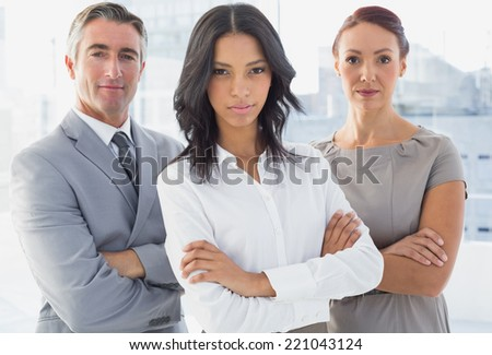 Serious businesswoman with folded arms at work - stock photo
