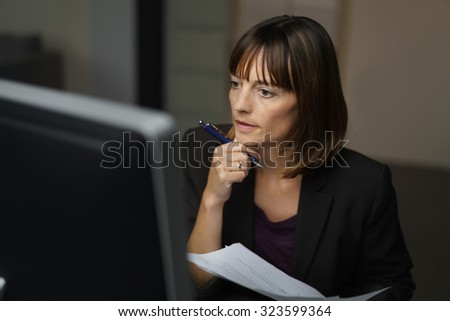 Serious Businesswoman Working on her Computer at her Desk Inside the Office. - stock photo