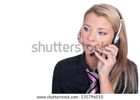 Serious call center agent holding her mouthpiece while looking at something - stock photo