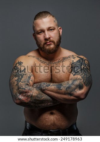 Serious calm musculed male with beard and tattooes