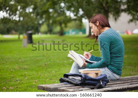 Serious casual student sitting on bench taking notes on campus at college - stock photo