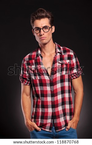serious casual young fashion  man standing with hands inpockets  and looking at camera  on dark background - stock photo