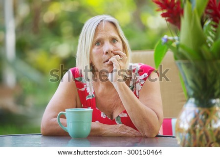 Serious Caucasian adult biting fingernails with worried expression  - stock photo