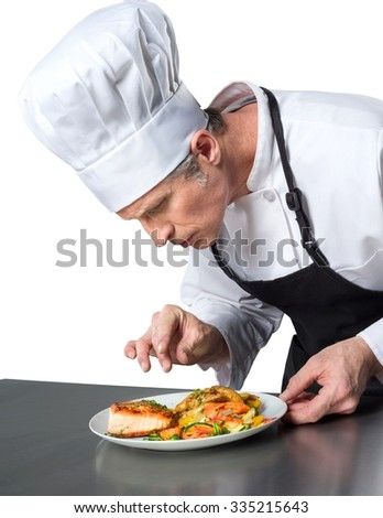 Serious Caucasian Chef in uniform preparing a meal - Isolated