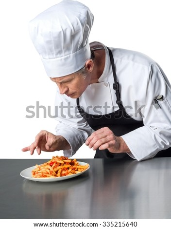 Serious Caucasian Chef in uniform scrutinizing the plateful of baked ziti  - Isolated