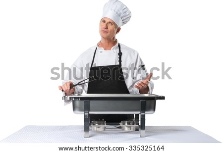 Serious Caucasian Chef in uniform standing behind a food warmer holding a two tined fork- Isolated - stock photo