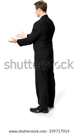 Serious Caucasian man with short black hair in business formal outfit pointing using palm - Isolated - stock photo
