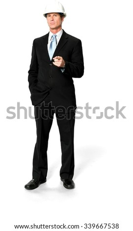 Serious Caucasian man with short black hair in business formal outfit with hands in pockets - Isolated