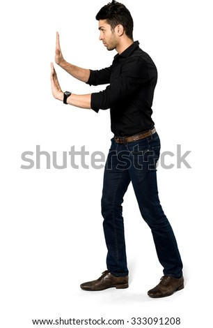 Serious Caucasian man with short black hair in casual outfit pushing - Isolated