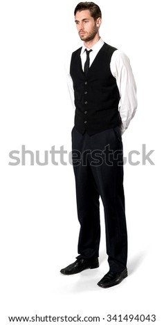 Serious Caucasian man with short dark brown hair in business casual outfit with hands behind back - Isolated