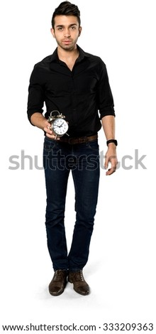 Serious Caucasian man with short dark brown hair in casual outfit holding alarm clock - Isolated