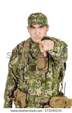Serious Caucasian Soldier In Green Camouflage Uniform pointing using finger - Isolated - stock photo
