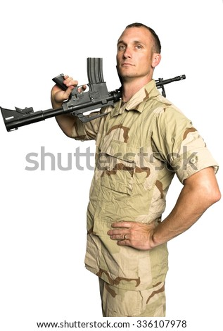 Serious Caucasian Soldier with short dark brown hair in Desert Camouflage Uniform holding machine gun - Isolated