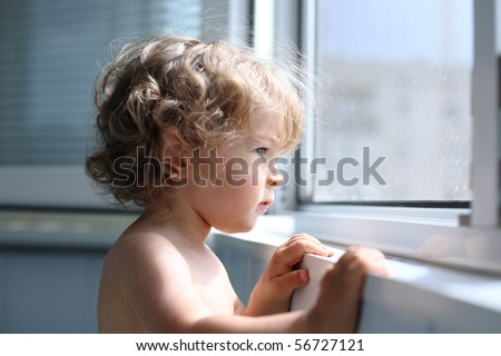 Serious child attentively looks out of the window - shallow depth of field - stock photo
