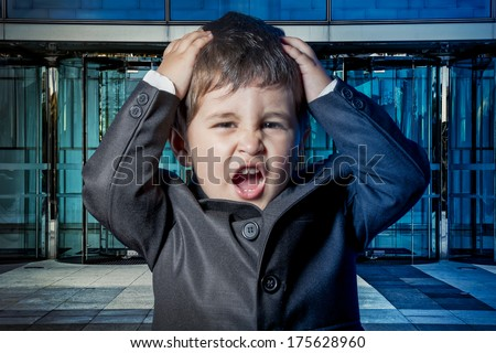 Serious child dressed businessman with hands in his tie and skyscrapers in the background - stock photo