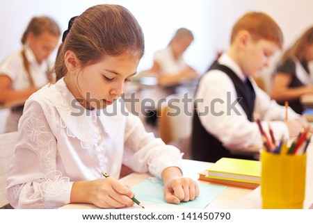 Serious children writing task in the school - stock photo