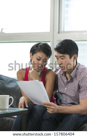 Serious Chinese couple reading a financial bill or document at home - stock photo