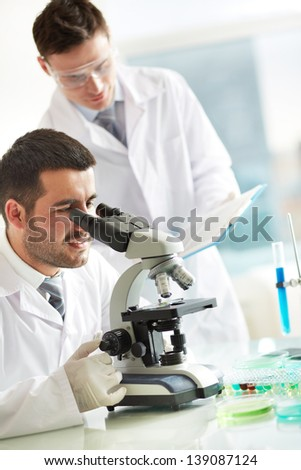 Serious clinician studying chemical element in laboratory with his co-worker standing near by - stock photo