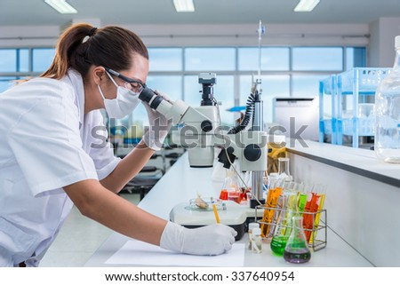 Serious clinician studying chemical element on tester and lecture in laboratory - stock photo