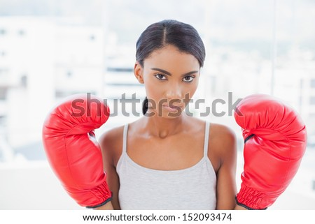 Serious competitive model with boxing gloves posing in bright room at home